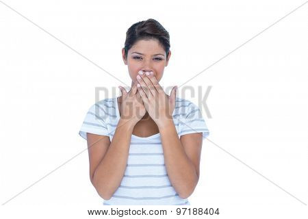 Pretty brunette hiding her mouth on white background