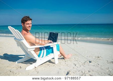 Man using laptop on deck chair at the beach on a sunny day