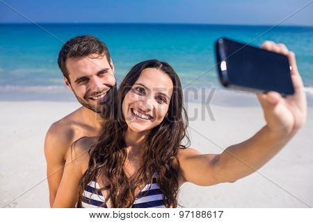 Happy couple taking a selfie at the beach on a sunny day
