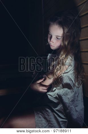 A Sad Little Girl Hugging A Doll At Home