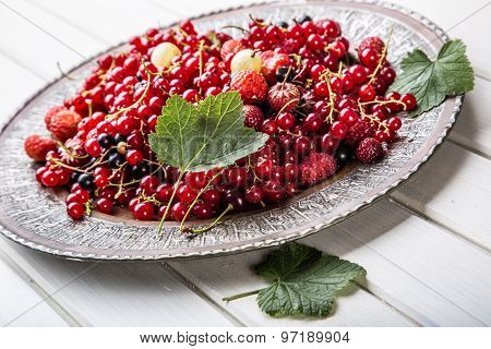 Red currant sponge cake. Plate with Assorted summer berries, raspberries, strawberries, cherries, cu