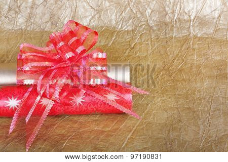 Rolls of multicolored wrapping paper with red bow for gifts on gold abstract background