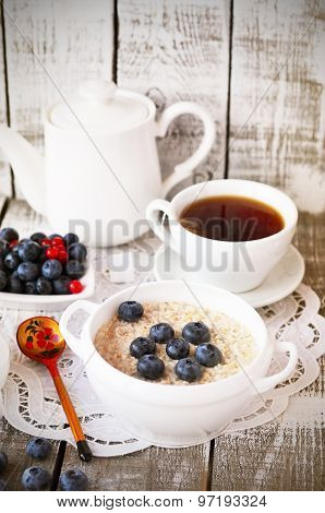 Porridge with blueberry and cup of tea on the vintage napkin on the white wooden background, Russian