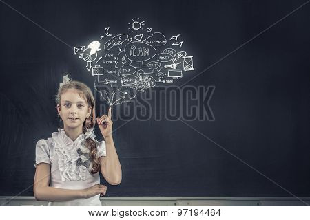 School girl writing graphs on blackboard with chalk