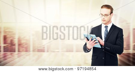 Unsmiling businessman using tablet pc against window overlooking city