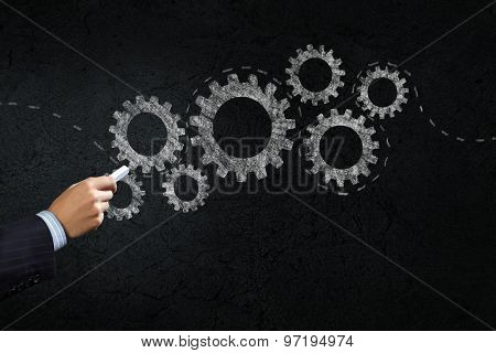 Close up of hand drawing gears mechanism with chalk