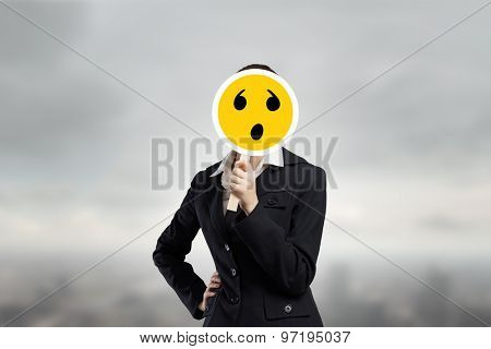 Unrecognizable businesswoman hiding her face behind mask