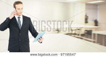 Serious businessman on the phone holding tablet against empty class room