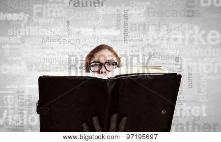 Young woman in glasses with opened book in hands