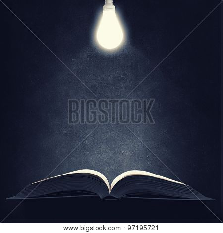 Old opened book and lamp hanging above