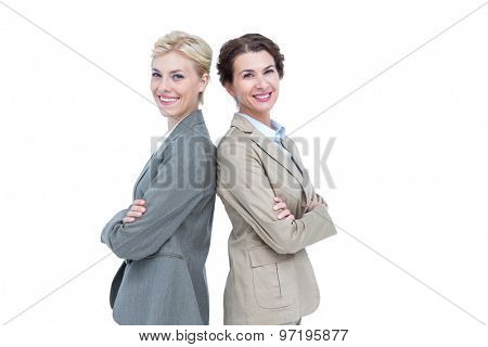 Serious businesswomen standing back on back against a white background