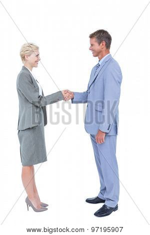 Smiling business people shaking hands against a white screen