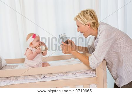 Happy mother taking a picture of her baby girl at home in bedroom