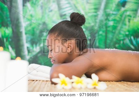 Pretty woman with salt scrub on the back at the health spa