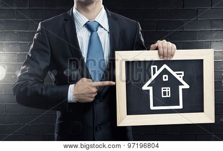 Unrecognizable businessman holding wooden frame with house sketch