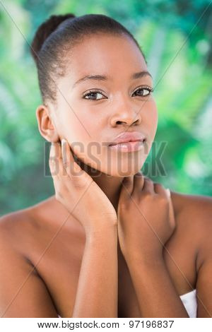 Close up of a beautiful young woman holding flower over white background