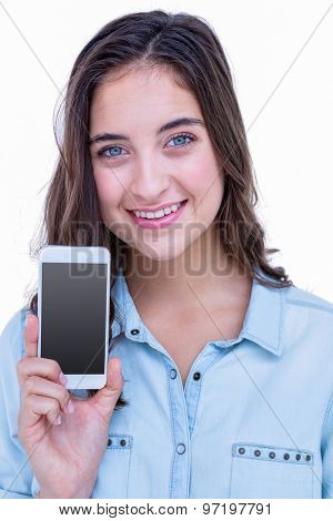 Pretty brunette smiling at camera with her smartphone on white background