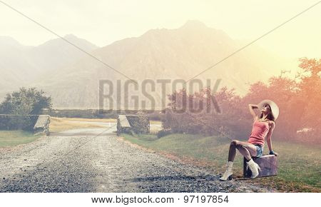 Traveler woman sits on retro suitcase and waiting for car