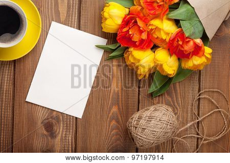 Colorful tulips bouquet, blank greeting card and coffee cup on wooden table