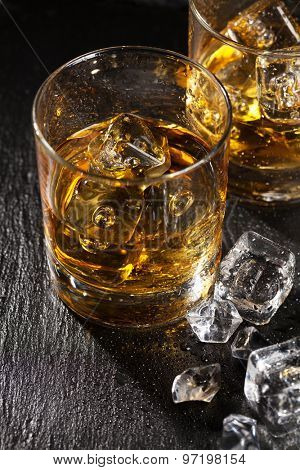 Glasses of scotch whiskey with ice on black stone table