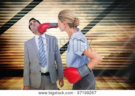 Businesswoman punching colleague with boxing gloves against window overlooking city