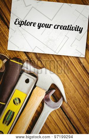 The word explore your creativity and digital tablet displaying blueprint against white card