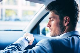 stock photo of retarded  - Handsome businessman looking on wrist watch in car - JPG