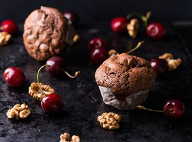 stock photo of chocolate muffin  - Chocolate muffins on dark background walnuts cherries and chocolate chunks as decoration selective focus - JPG