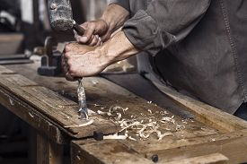 stock photo of chisel  - Carpenter with a hammer and chisel on the wooden workbench in carpentry - JPG