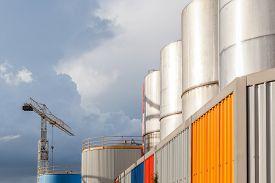 image of petrol  - The big petrol oil tanks and hoisting crane againt blue sky in refinery industry - JPG