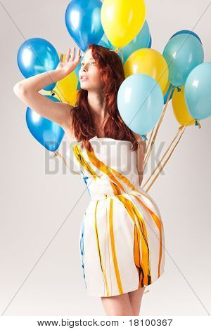 red hair woman in short elegant silk dress with a lot of yellow and blue balloons around her, studio shot