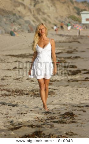 Young Woman In A White Dress Walking On The Beach At Sunset.