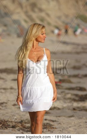 Beautiful Woman In White Dress Walking At The Beach.