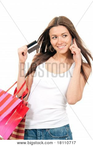 Pretty Young Woman Holding Shopping Bags And Talking By Phone