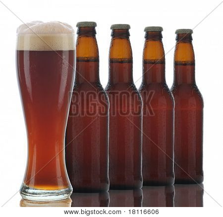 Four Brown Beer Bottles and a Full Glass of dark ale on a white background.