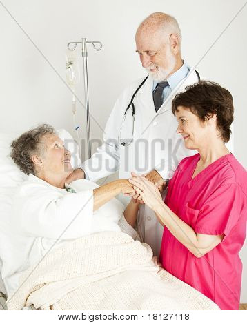 Attentive doctor and nurse caring for an elderly hospital patient.