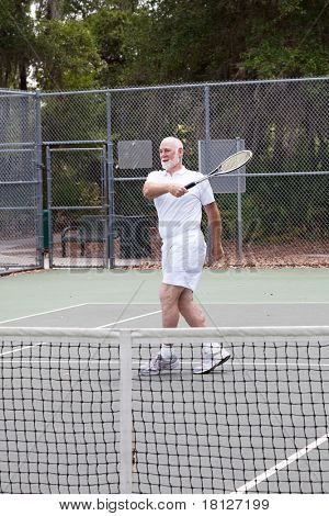 Active senior man plays tennis for exercise and fun.