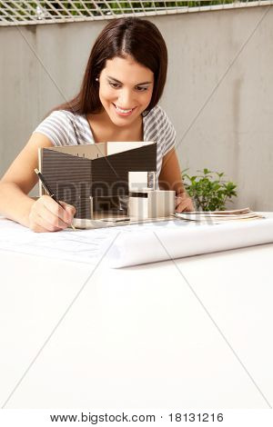 A young female architect working on a model and blueprints