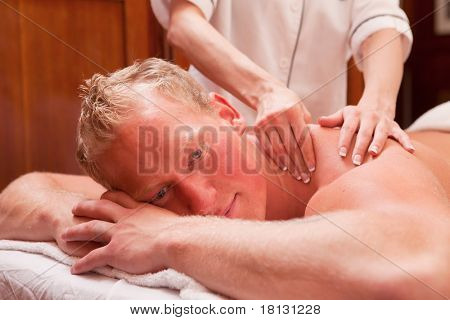 A detail of a man receiving a back and shoulder massage in an old style spa