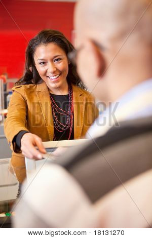 Passing over credit card to shop assistant after shopping