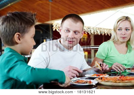 Portrait of family of three eating pizza in cafe