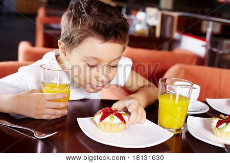 Portrait of cute lad with glass of juice looking at tasty cake in cafe