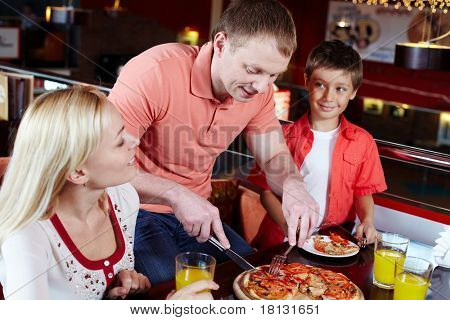 Portrait of happy family spending time in pizzeria
