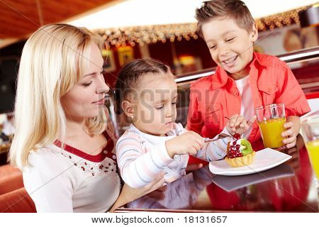 Portrait of cute girl eating cupcake with her mother and brother near by in cafe
