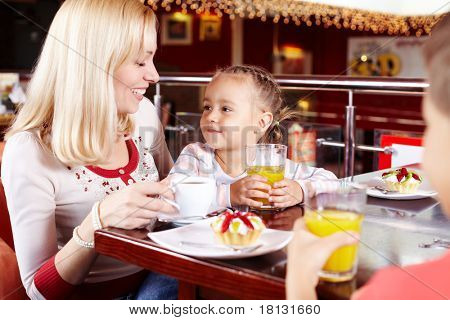 Portrait of cute children and their mother in cafe