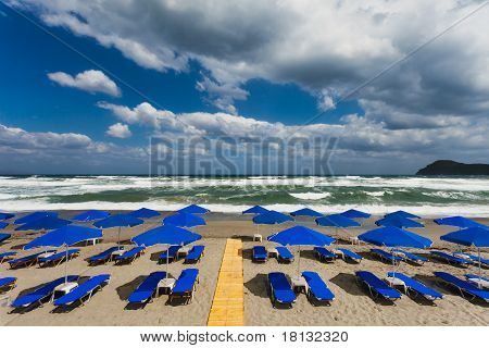 Blue Parasols At An Empty, Stormy Beach