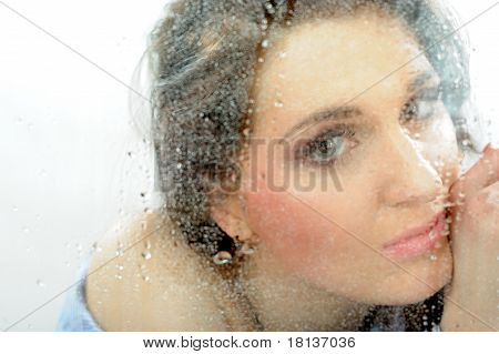 Pretty Lonely Girl Looking Throw The Rainy Window. Focus On Raindrops