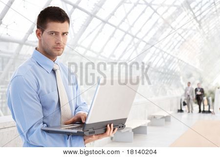 Handsome young businessman working on laptop at modern office lobby.?
