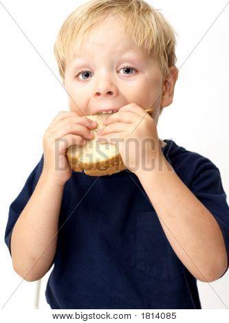 Niño comer sándwich de mantequilla de maní