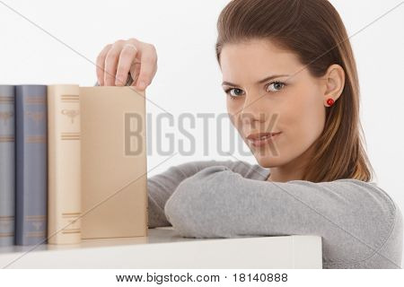 Attractive woman standing by shelf with books, looking at camera, smiling.?